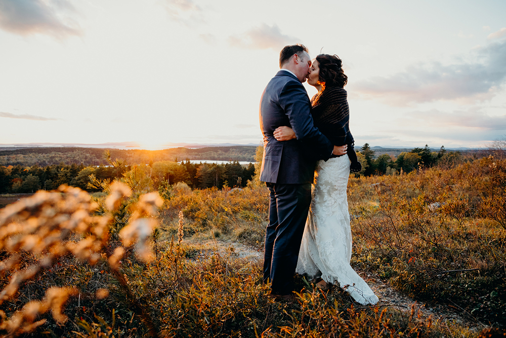 A couple kiss during sunset at their Acadia National Park elopement ceremony