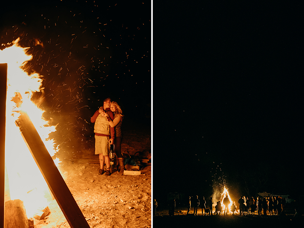 Newlyweds embrace with friends and family around a giant bonfire at a backcountry utah wedding
