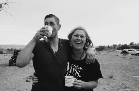 Couple laugh and embrace while drinking coffee before their backcountry utah wedding