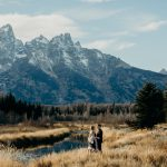 Couple in non-traditional wedding attire embrace after their Grand Teton National Park elopement at Schwabacher Landing
