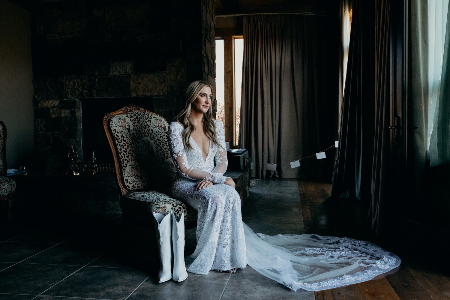 Bride sits in ranch house with white cowgirl boots as she gets ready for her intimate Jackson Hole wedding