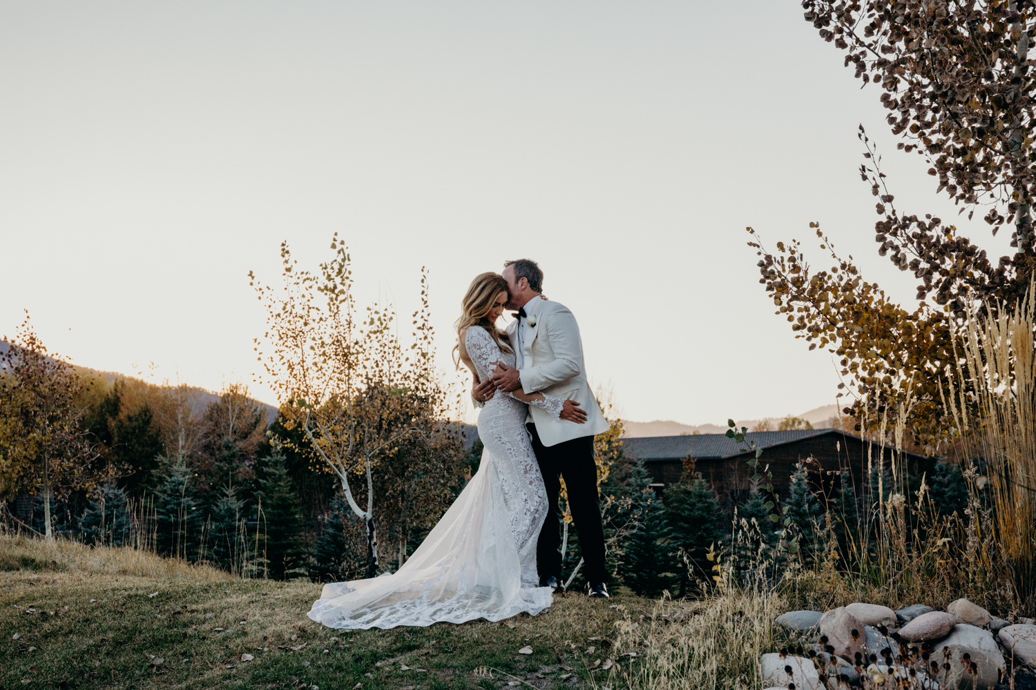 Couple embrace on a hillside during sunset at their Jackson Hole wedding