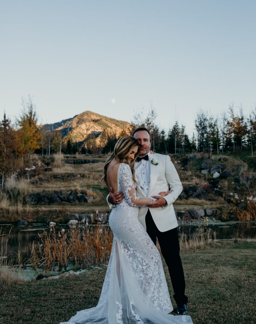 A bride wearing a beautiful lace Berta gown embraces groom as moon rises in Jackson Hole, Wyoming