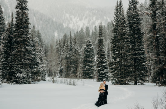 Man in black suit holds woman in black gown amongst snowy trees in Teton Pass during Jackson Hole engagement photos