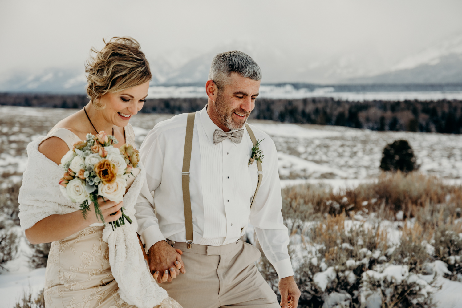 A couple smile and hold hands as they walk out of their Grand Teton National Park Jackson Hole winter elopement ceremony