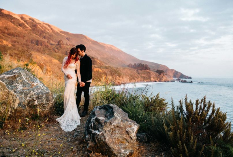 Man in black suit embraces new wife wearing Claire Pettingbone lace gown during sunset along the Pacific Coast in Big Sur