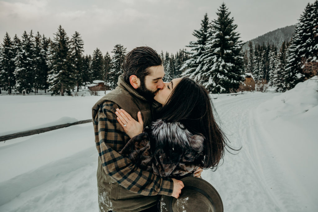Couple kiss on Trail Creek Ranch in Jackson Hole Wyoming during their engagement photos with Erin Wheat