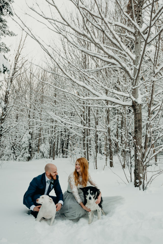 A couple smile lovingly at one another with their dogs in snowy Vermont woods after their winter elopement