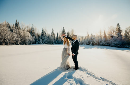 Man and woman dance in a snowy field at their winter elopement in Northern Vermont
