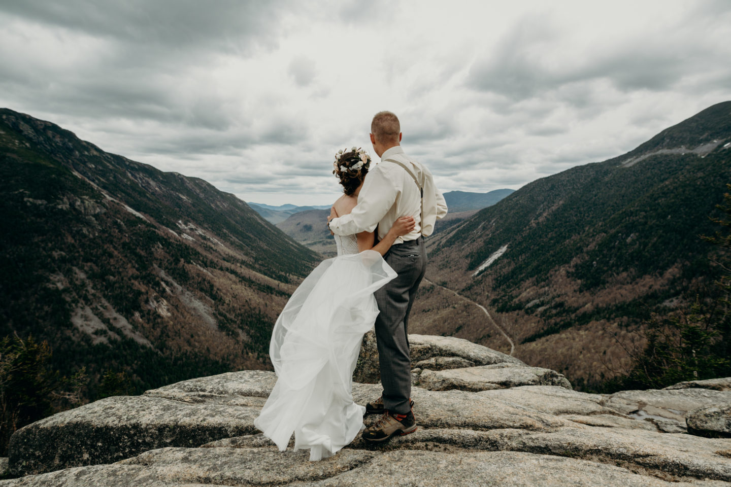 A couple embrace and face the valley and mountains below them on top of Mount Willard after their wedding