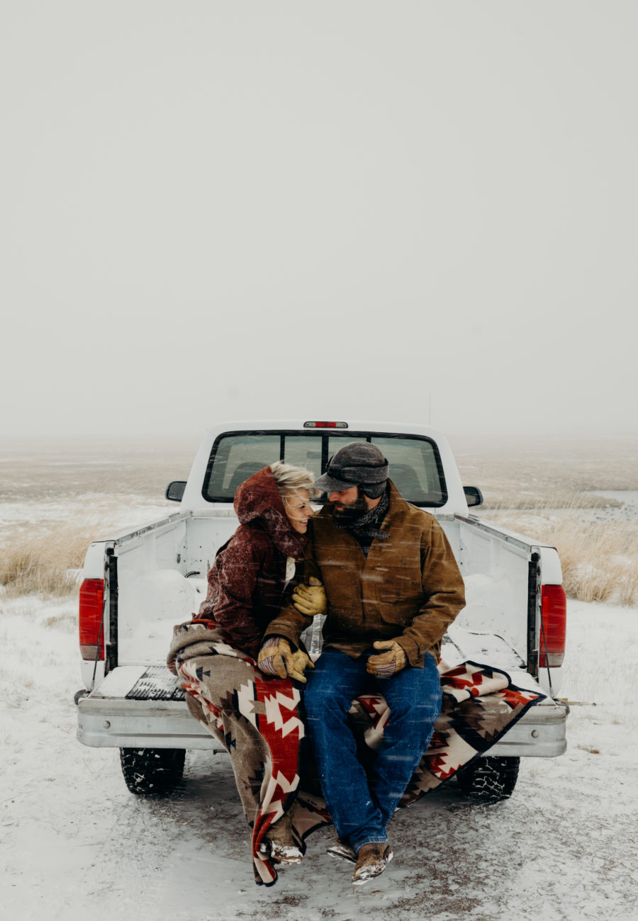 A couple wearing Filson sit together on the back of white ford truck in a snowstorm in Jackson Hole, Wyoming