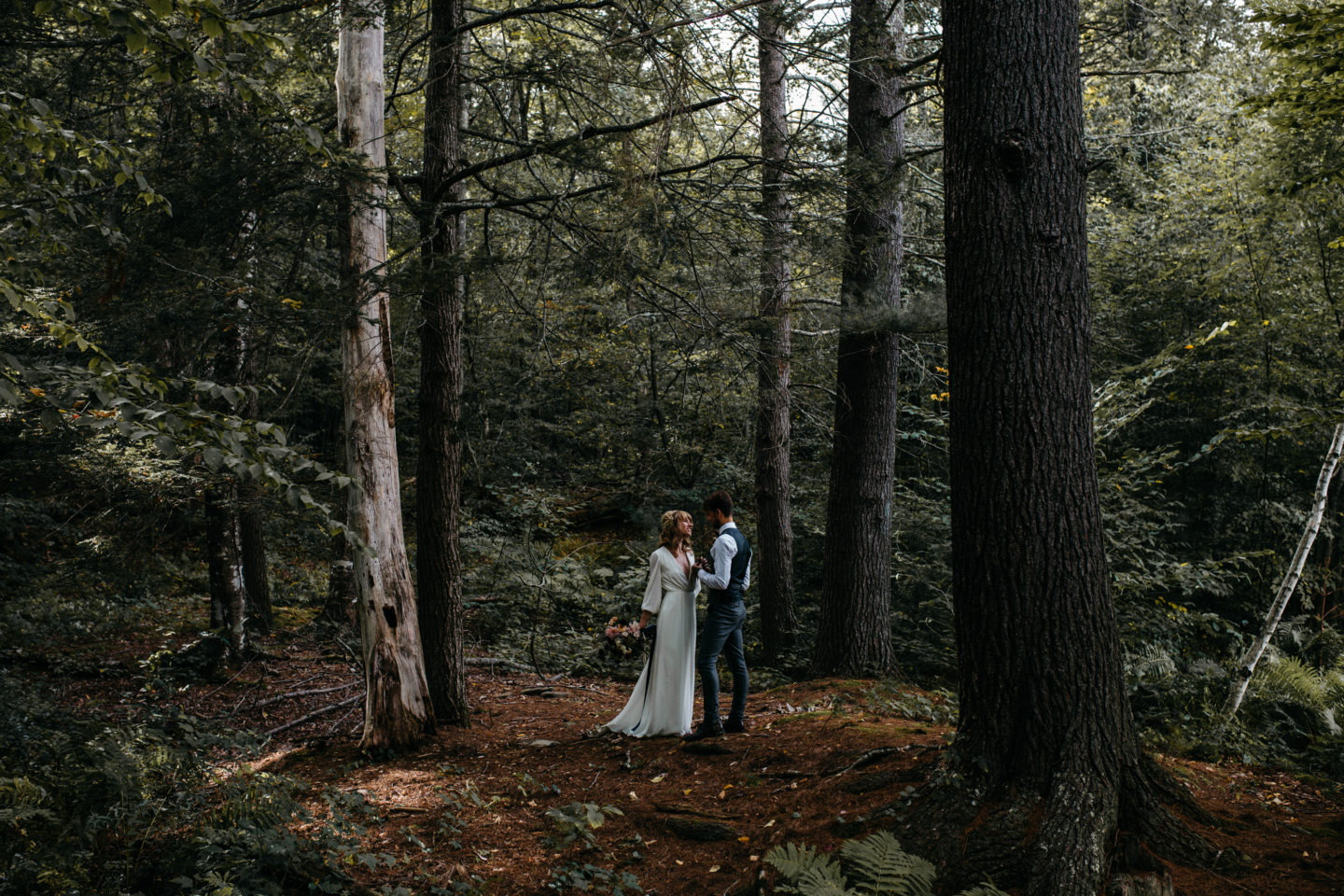 Newly wed couple face one another in moody woods outside of Foxfire Mountain House wedding photograph by Erin Wheat