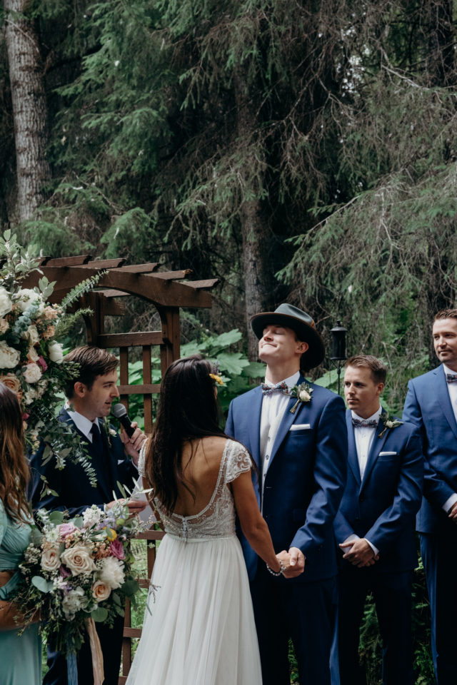 Groom wearing Stetson hat closes eyes and looks toward the heavens while holding his brides hands as they are married in Girdwood Alaska