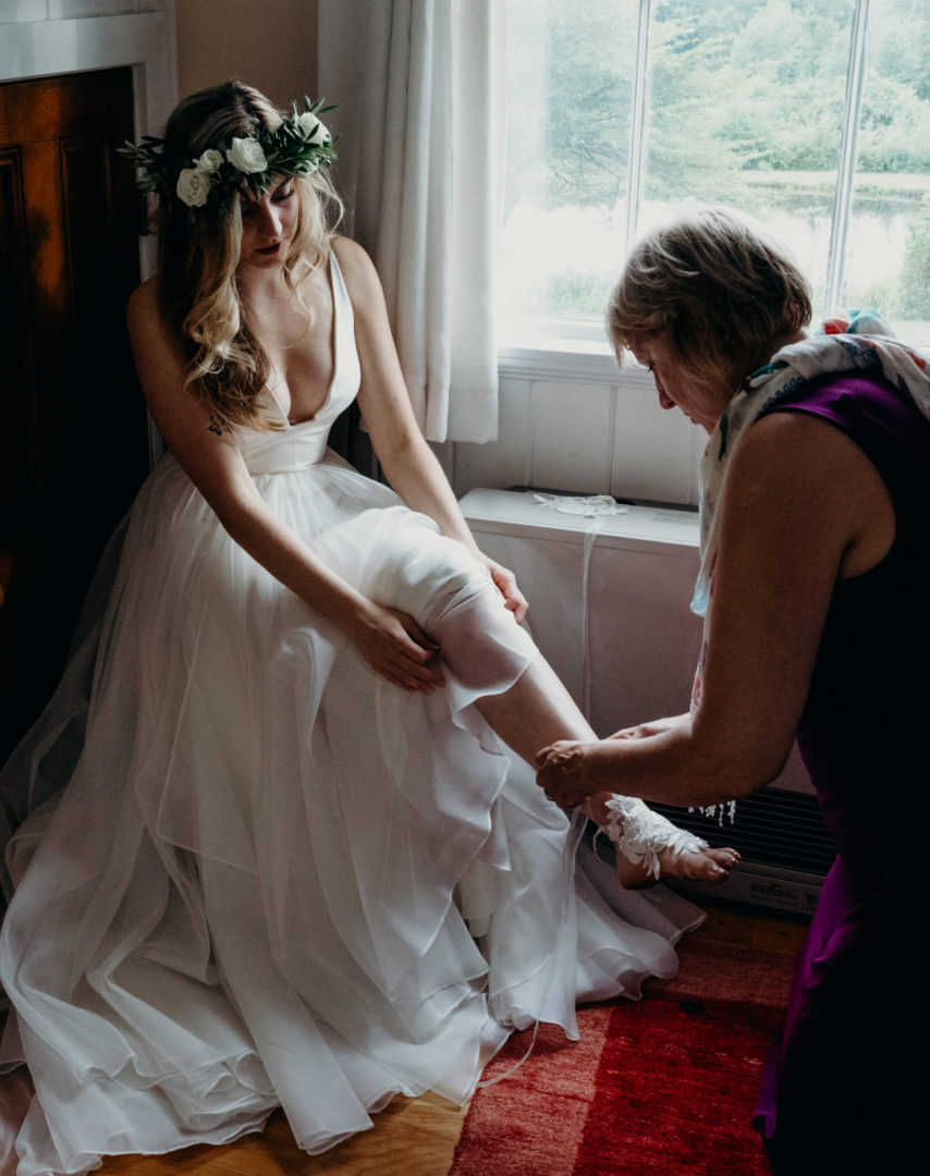 Mother and daughter sit in front of a windown as mother helps her daughter put on lace shoes for wedding ceremony