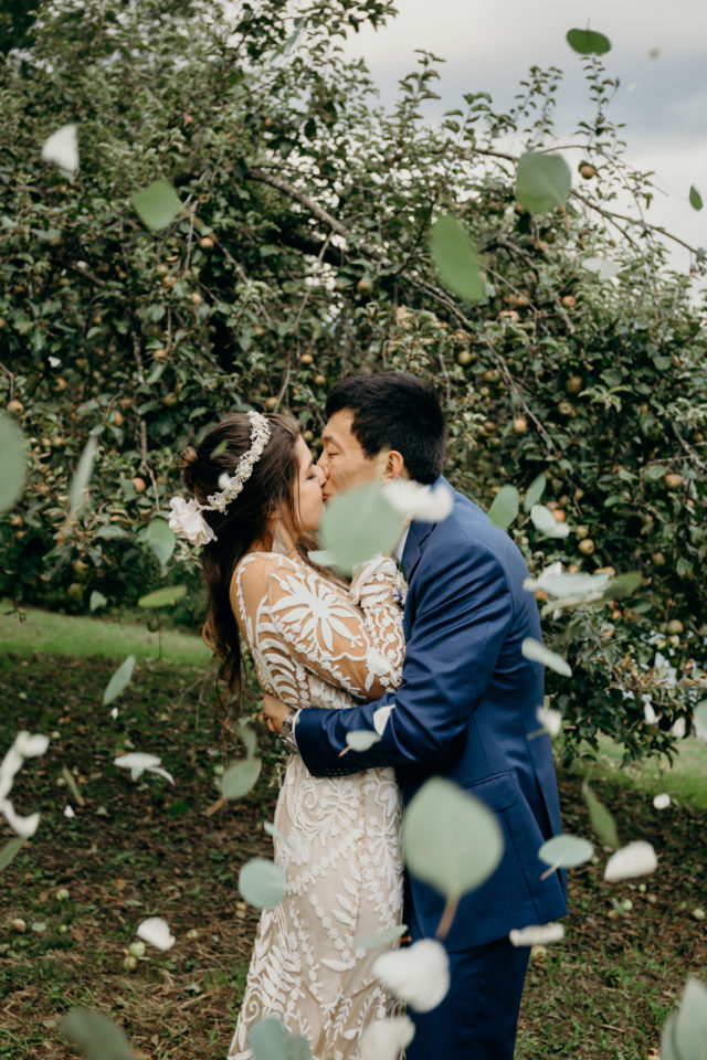 Bride wearing Rue de Seine dress kisses groom as leaves and petals fall around them