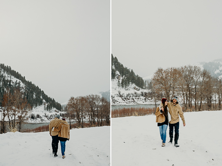 Couple walk together along a frozen Snake River wearing jeans and Vans and smiling