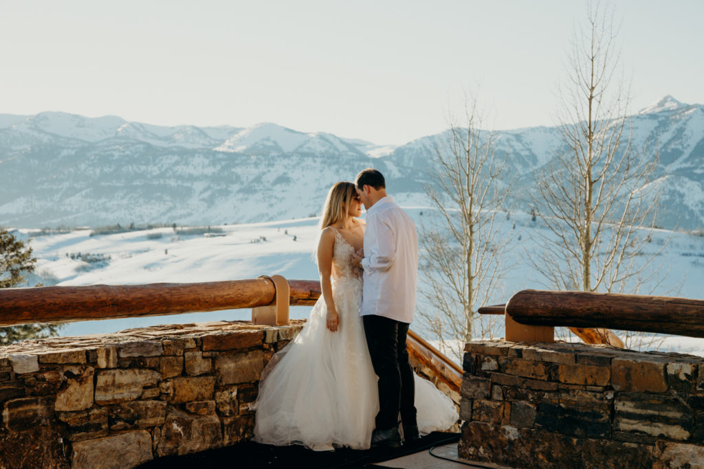 couple pose face to face in wedding attire at Amangani resort in Jackson Hole Wyoming at sunset