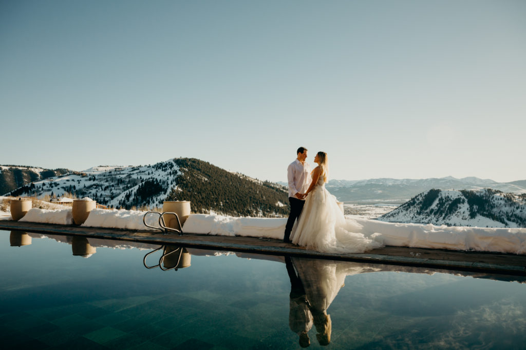 Couple stand together during wedding portraits as their silhouettes are reflected in Amangani Resort's pool in Jackson Hole, Wyoming